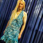 Ein Mann (Markus) mit einer langen blonden Perücke, einer Perlenkette und einem kurzen blauen Paliettenkleid steht vor einem blauen Vorhang