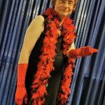 Ein Mann (Volker) mit einer dunkelblonden Kurzhaar-Perücke, einer roten Federboa, roten Handschuhen und einem langen schwarzen Kleid steht vor einem blauen Vorhang